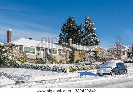 Snow Covered Residential House With Car In Snow On The Road