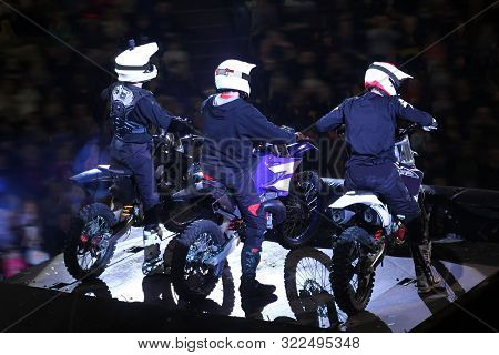 Back View Of Three Motorcross Racers In Helmets On Stage
