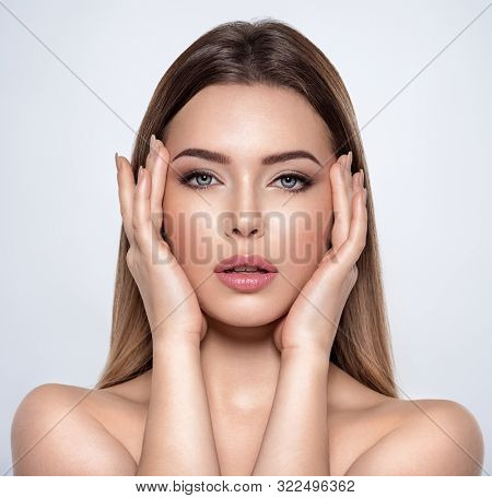 Beauty face of the young beautiful woman  with a fresh healthy skin. Closeup portrait of an attractive female with a beautiful eyes. Skin care concept. Model with a smokey eye makeup. Beauty treatment