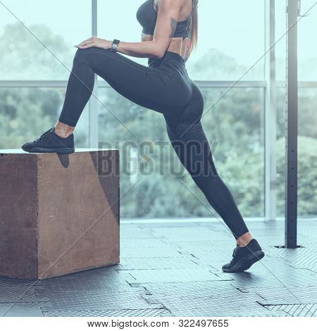 Legs Of Slim Athletic Woman Doing Stretching Exercise With Jump Box, Image With Cold Vintage Toning