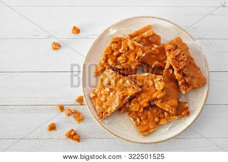 Plate Of Traditional Peanut Brittle Candy Pieces. Top View On A White Wood Background.