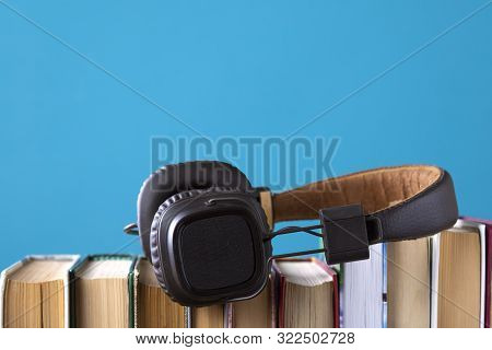 Headphones And Books But Against Blue Background, Concept Of Audio Books, Listening To A Book.