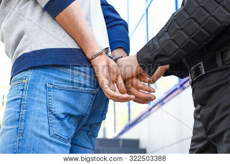 Police Officer Putting Handcuffs On Criminal Outdoors, Closeup