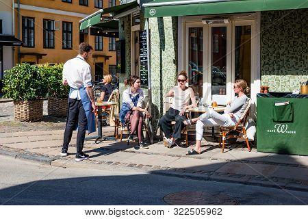 Copenhagen, Denmark - May, 2019: Street Life In Copenhagen. People Relaxing In A Street Cafe.