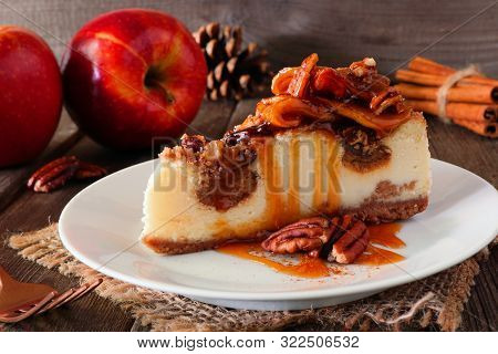 Caramel Apple Pecan Cheesecake.  Close Up Side View With A Rustic Wood Background. Autumn Dessert.