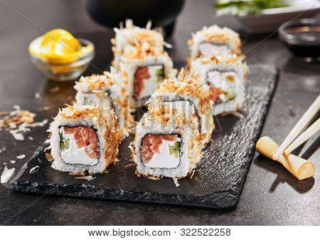 Macro shot of uramaki sushi rolls with cream cheese, salmon, tuna shavings or dried bonito, cucumber, nori. Portion of fresh katsuobushi roll in Japanese restaurant closeup poster