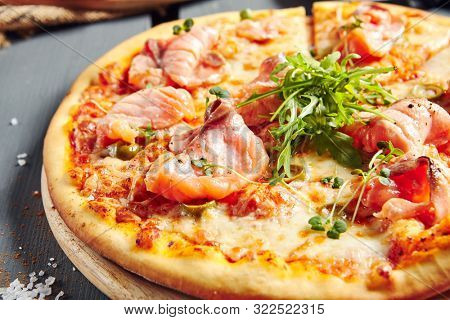 Italian Pizza Restaurant Menu - Pizza with Smoked Salmon and Rocket Salad. Pizza Dinner. Closeup Salmon Pizza
