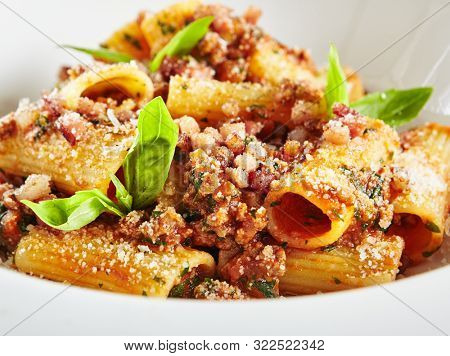 Exquisite Serving White Restaurant Plate of Homemade Rigatoni with Bolognese Sauce and Smoked Pork Belly Close Up. Stylish High Kitchen Italian Penne Pasta Tubes on Natural Black Marble Background