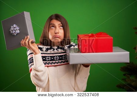 Adult happy woman with Christmas gift over green background