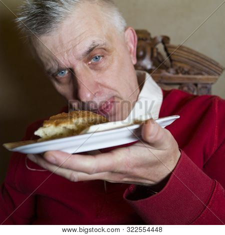 Particular Focus Shot Of A Hungry Man Holding Abstract Dish On A Plate, Studio Portrait. Shallow Dor