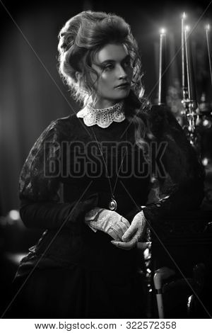 The Victorian era concept. Beautiful woman in elegant historical dress and hairstyle posing in vintage interior. Baroque. Fashion. Black-and-white portrait.