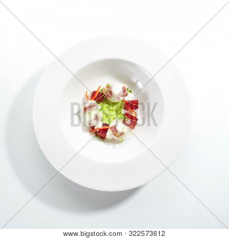 Exquisite serving tuna with kohlrabi and celery dressing with lime on white restaurant plate isolated. High cuisine restaurent dish with delicious yellowfin sashimi tartar in minimalist style topview poster