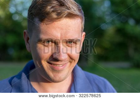 Portrait Of A Young Man On Nature Background. Emotion Facial Expression. Smug Smile, Feelings And Pe