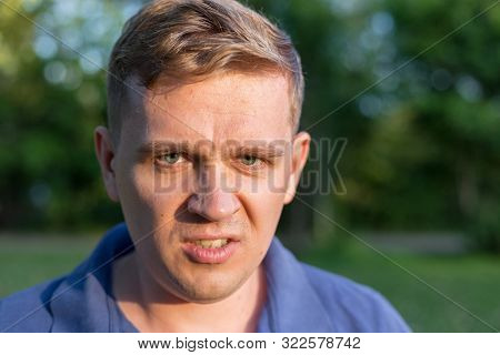 Enraged Infuriated Man Baring His Teeth. Portrait Of A Young Man On Nature Background. Emotion Facia