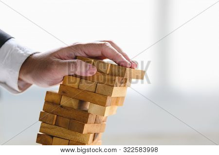 Businessman Collapsing Stacked Tower Wood Block By Hand As Failure Or Bankrupt Project. Business Org