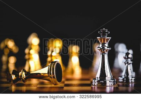 Closeup king chess piece defeated enemy or trade competitor by checkmate at end of chessboard game. Businessman moving chess to success competition by hand. Leadership and strategy management poster