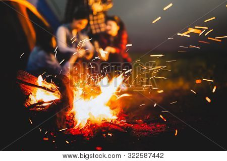 Sparking Bonfire With Tourist People Sit Around Bright Bonfire Near Camping Tent In Forest In Summer