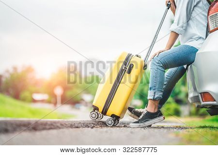 Closeup Lower Body Of Woman Leg Relaxing On Car Trunk With Trolly Luggage Along Road Trip With Autum
