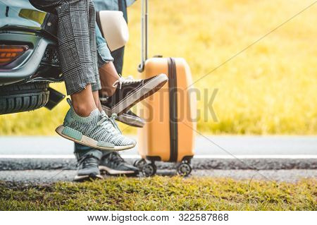 Closeup Lower Body Of Group Of Friends Relaxing On Suv Car Trunk With Yellow Trolly Luggage Along Ro