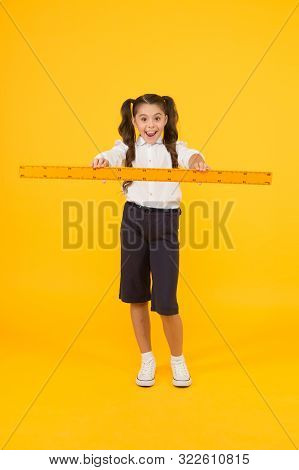Drawing Straight Lines At Geometry. Happy Small Girl Holding Ruler For Geometry Lesson On Yellow Bac