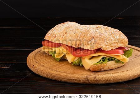 Ciabatta Sandwich With Lettuce , Prosciutto And  Cheese On Wooden Board With Copy Space.