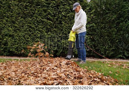 Autumn Gardening. A Young Woman Cleans The Leaves With A Blower.