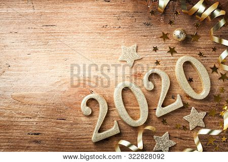 Happy New Year Festive Background With Golden Numbers 2020 And Christmas Decorations On Vintage Wood