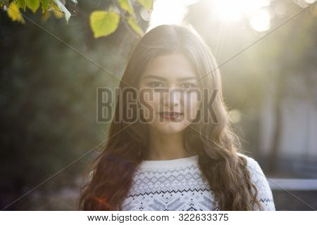Excited happy fall woman smiling joyful and blissful holding autumn leaves outside in colorful fall forest. Beautiful energetic europe race young woman. poster