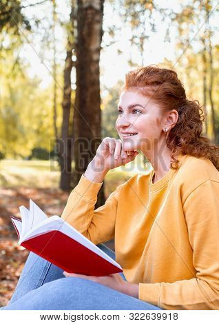 Smiling Happy Red Hair Student Girl Reading A Book Outside In Autumn Park