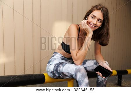 Image of happy smiling woman in sportswear listening music with earpods and holding cellphone while sitting on parking outdoors