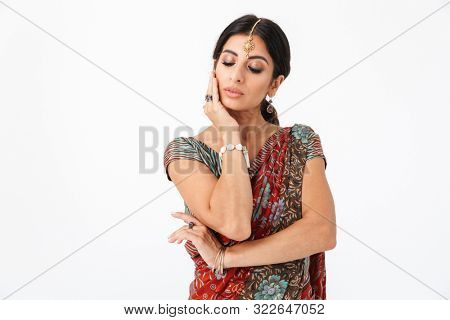Portrait of adorable hindus girl wearing traditional indian costume lehenga choli or saree dress and ethnic jewelry isolated over white background