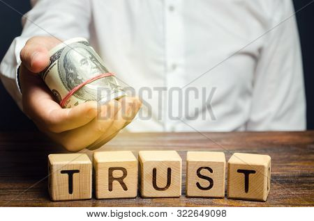 Wooden Blocks With The Word Trust And Money In The Hands Of A Businessman. Trust Relationships Betwe