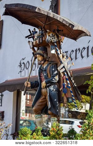 Oberammergau, Germany - Oktober 09, 2018: Wooden Sculpture Of A Tramp With Umbrella In Old-fashioned