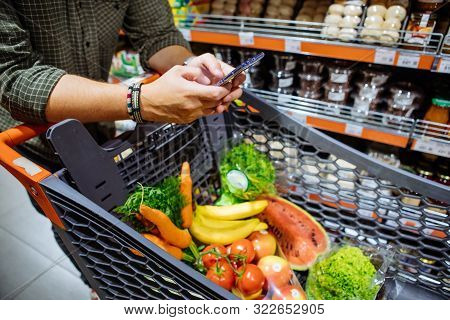 Man With Smartphone Do Shopping In Grocery Store Copy Space