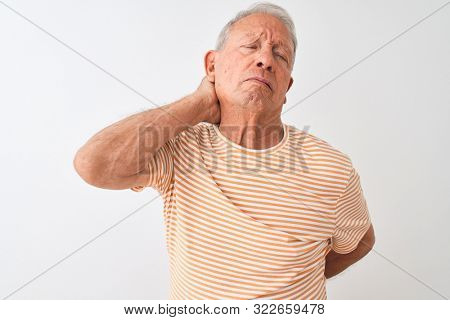Senior grey-haired man wearing striped t-shirt standing over isolated white background Suffering of neck ache injury, touching neck with hand, muscular pain