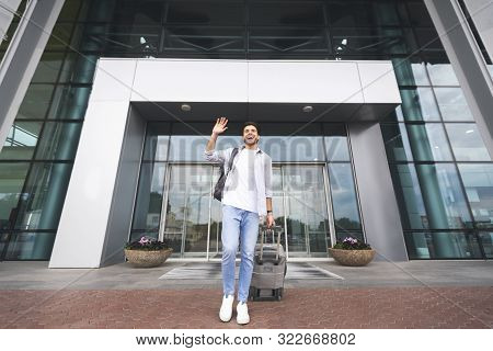 Homecoming. Happy Man Arrived Home, Waving Hand While Going Out Of Airport Building, Free Space