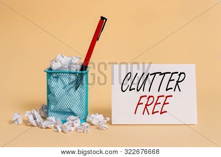 Text sign showing Clutter Free. Conceptual photo Well organized and arranged Tidy All things in right places crumpled paper trash and stationary with note paper placed in the trash can. poster