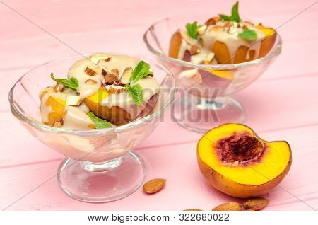 Baked Peaches Dessert In An Ice-cream Bowl Topped Sabayon Cream With Almond And Mint Against The Pin