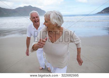 Happy senior couple having fun together at beach