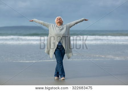 Happy senior woman doing stretching exercise on the beach