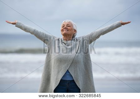 Happy senior woman with arms outstretched standing on the beach