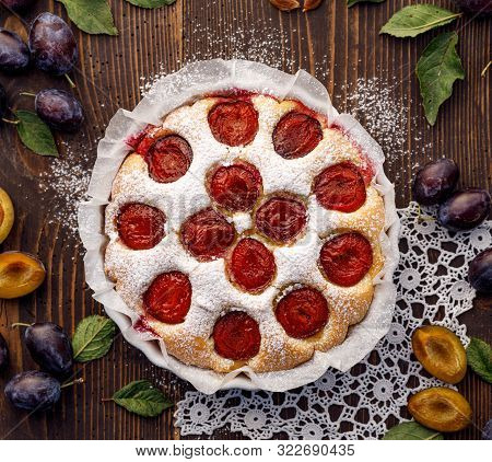 Plum Cake, Traditional Homemade  Cake With Sweet Plums, Sprinkled With Powdered Sugar On A Rustic Wo