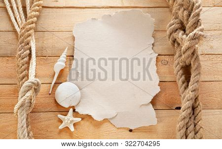 Old sheet of paper on board the ship. Shell and starfish. Wooden background.
