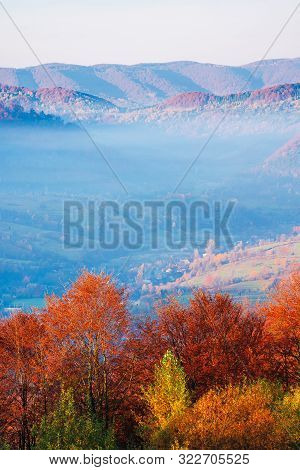 Beautiful Morning Scenery In Mountains. Light Passes Through Rising Fog In The Distant Valley. Wonde