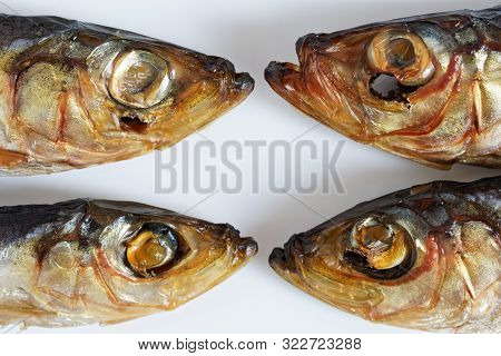 Four Smoked Baltic Herring On A White Background. The Metaphor Of The Relationship Between People: C