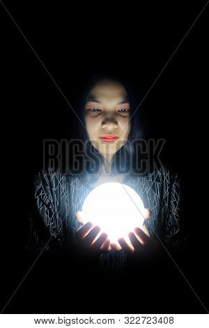 Beautiful Woman Holding Bright White Light In The Dark Black Background.