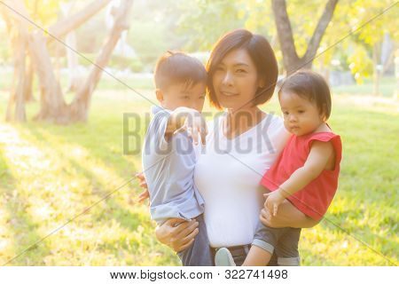 Beautiful Young Asian Mother Carrying Little Boy And Girl In The Park, Asia Woman Happy Having Son A
