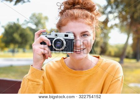 Smiling Happy Red Hair Student Girl Taking Picture With Old Vintage Camera Outside In Autumn Park