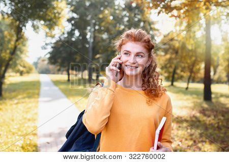 Smiling Happy Red Hair Student Girl Talking On The Phone Outside In Autumn Park