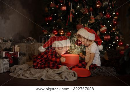 Family On Christmas Eve At Fireplace. Kids Opening Xmas Presents. Children Under Christmas Tree With